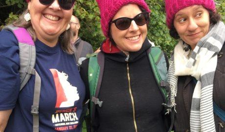 Photograph of three women wearing pink pussyhats