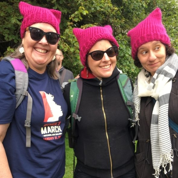 Photograph of three women wearing pink pussyhats