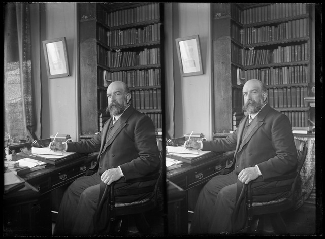 A man sits at his ornate desk in a room featuring a very large bookcase, posing with pencil on pad as if he is writing