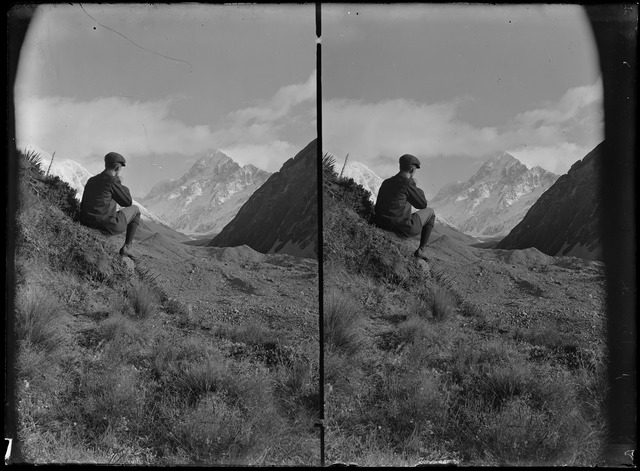 A man poses on a hill with Mt Cook in the distance