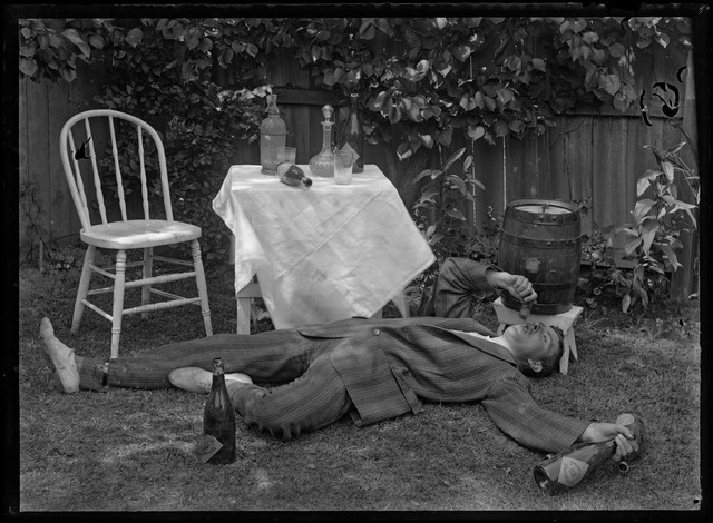 Depicts a male figure lying, with limbs sprawled, on the grass before a table with a number of glasses, bottles and decanters atop. The male wears a pinstriped suit and has a bottle of champagne in one hand and small glass in the other, tipped towards his open mouth. To the left of the etching is a chair. The scene is set in a garden, with a fence, trees and small planters on the perimeter.