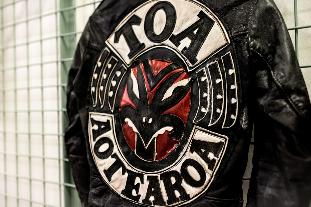 A patch on the back of a black leather jacket, the word 'Toa Aotearoa' are stitched on