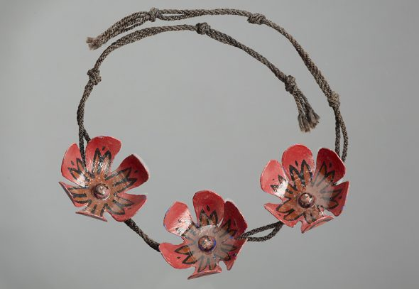 A necklace made by Colin McCahon. It features three handcrafted red flowers on a thin woven rop