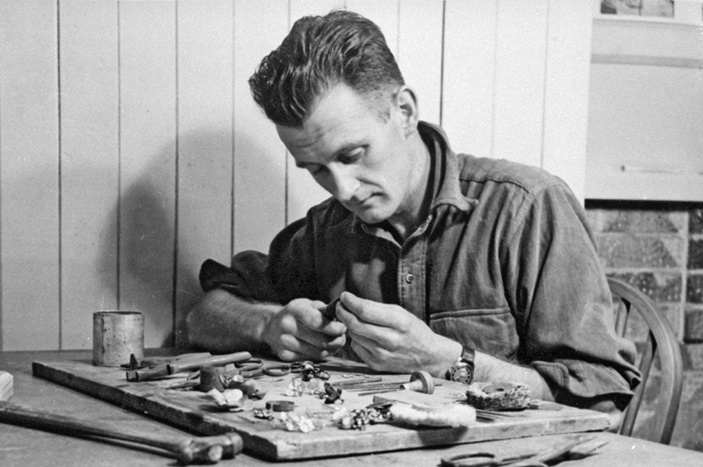 Colin McCahon sits at a table crafting a piece of jewellery. There are lots of tools on the table