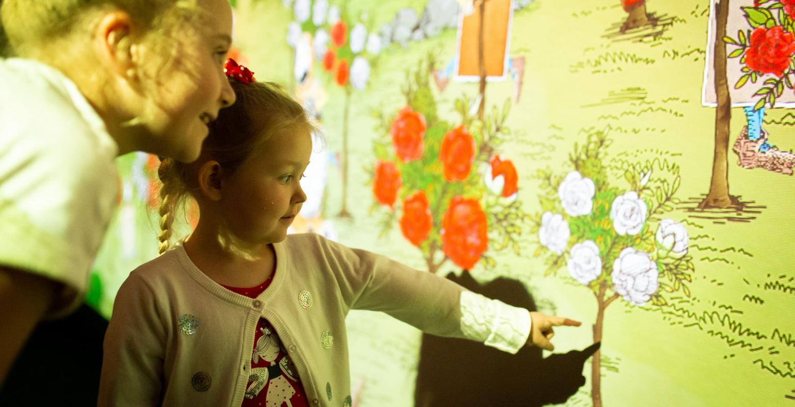 A little girl looks at a digital projection which includes red and white roses