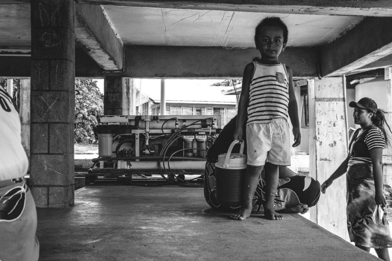 Child holds large thermos, he's standing under a building. Behind him is a water pump