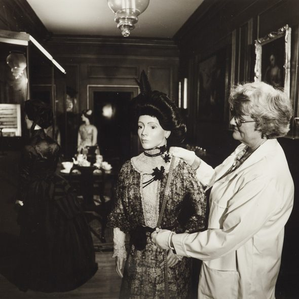 Valerie prepares a mannequin wearing a dress in an ornate room