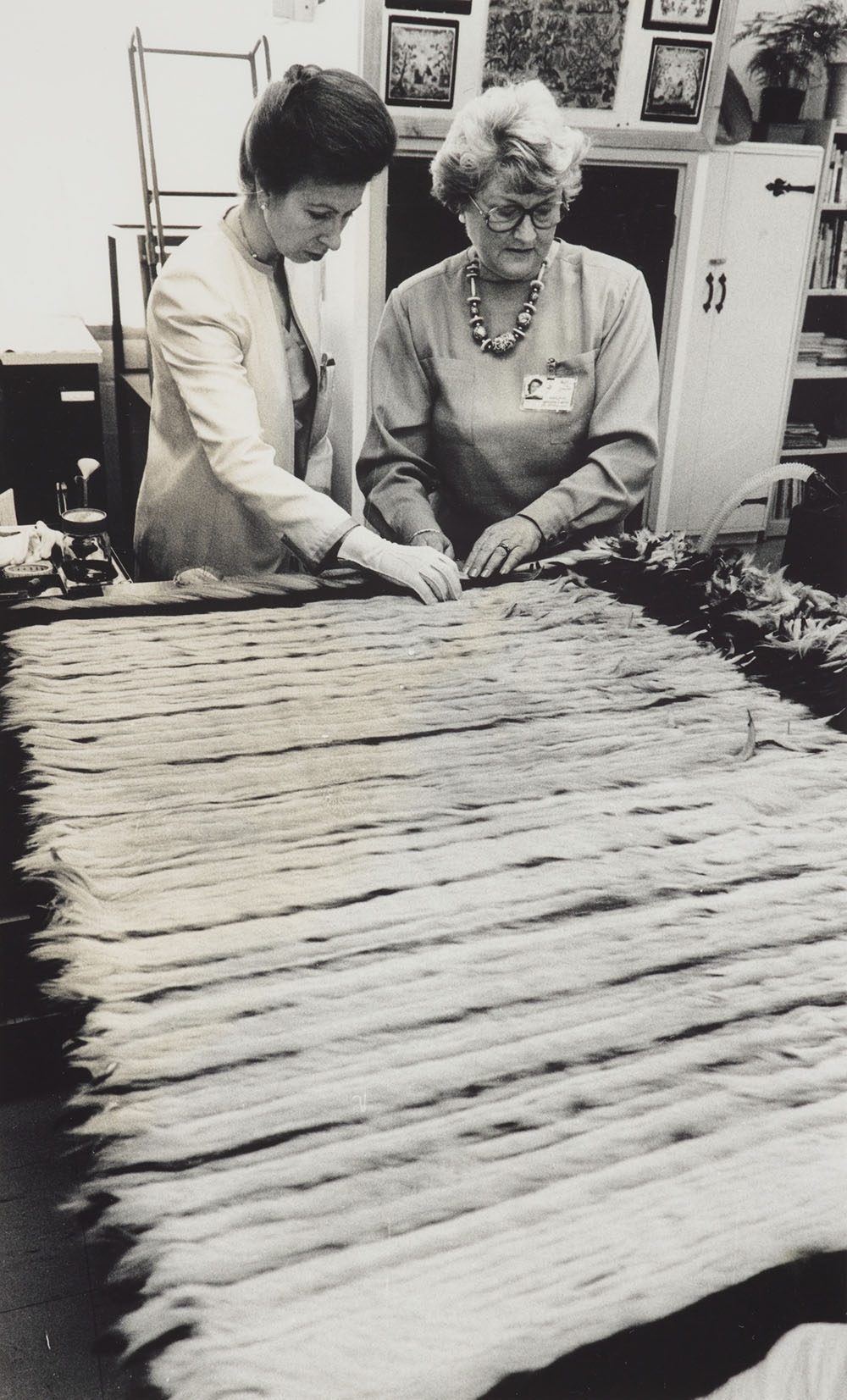 Two women examine a Māori cloak on a table