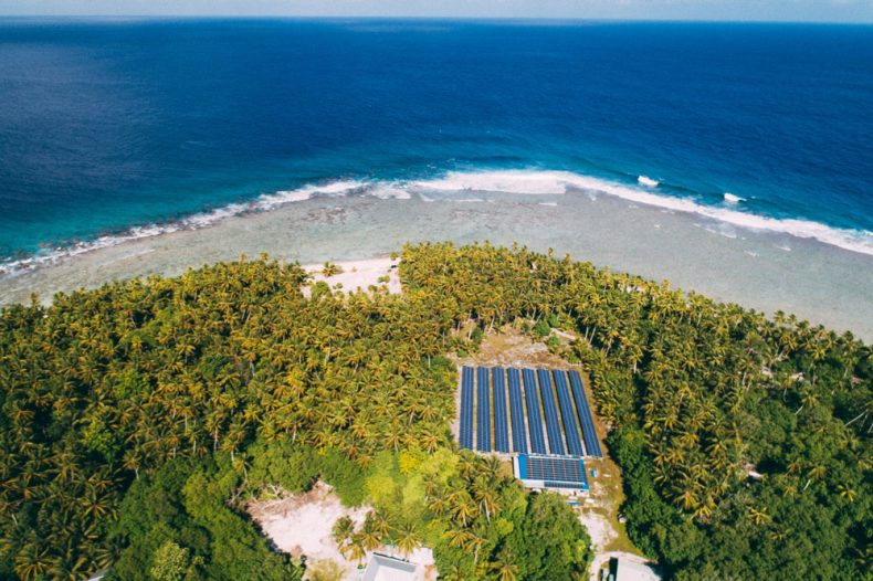 Aerial shot of the coast, large solar panels are on the land