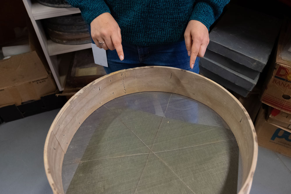 Hands point to a large sieve