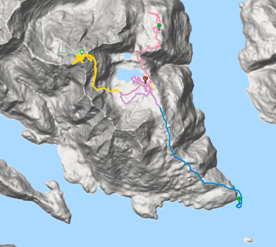 Grey computer-generated 3D map in style of a mould, surrounded by blue water. There are blue, pink, purple, yellow and green trails marked on the map.