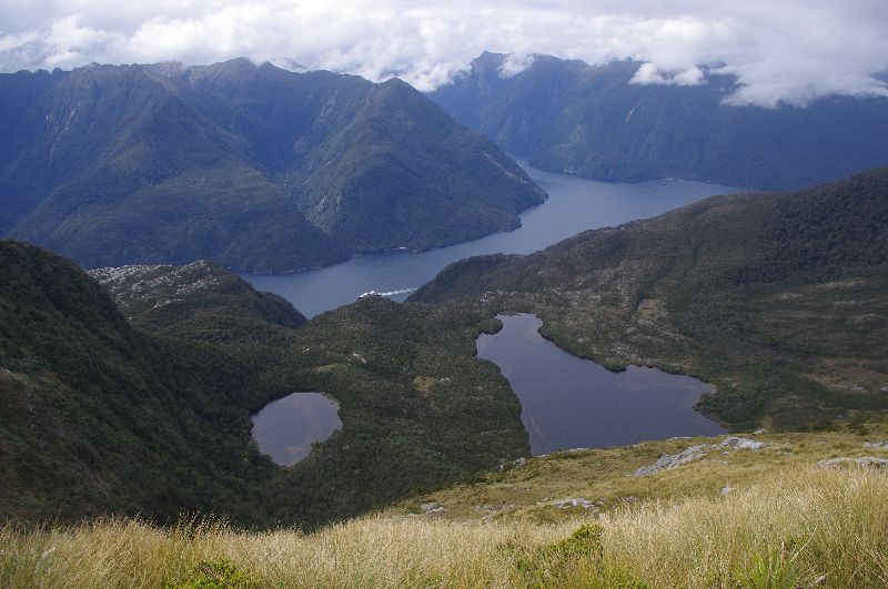 Looking down a grassy mountain at a lake and sea with inlets and coves, surrounded by green mountains and low cloud. A boat is on the water near the centre of the image.