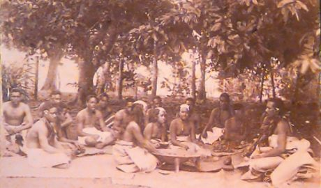 Sepia image of 15 people sitting on flax mats under trees