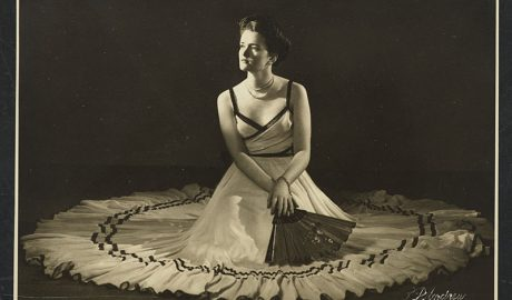 Sepia image of a woman sitting in the middle of a large white dress holding a fan