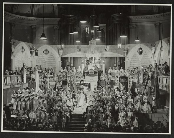 Black and white photo of many costumed people on stage arranged in the style of the Queen's coronation