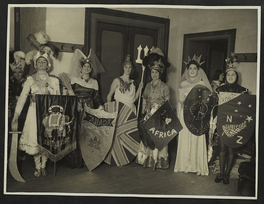 Sepia photo of 8 people in costumes depicting different countries holding sheilds with national symbols on them
