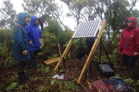 Four people in blue and red jackets standing in the bush next to a woodens structure with a metal solar panel attached.