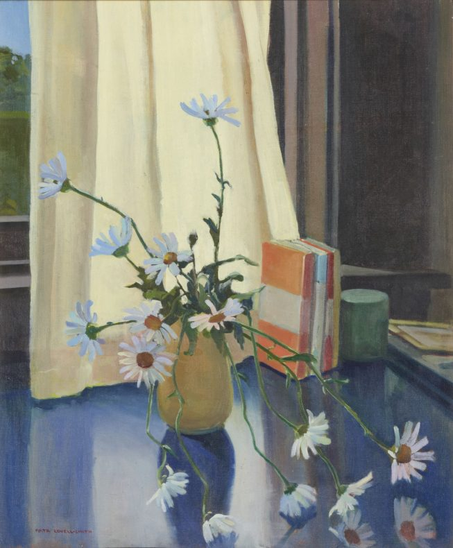 Vase of white daisies on a blue table top in front of a window, the cream curtain mostly drawn.