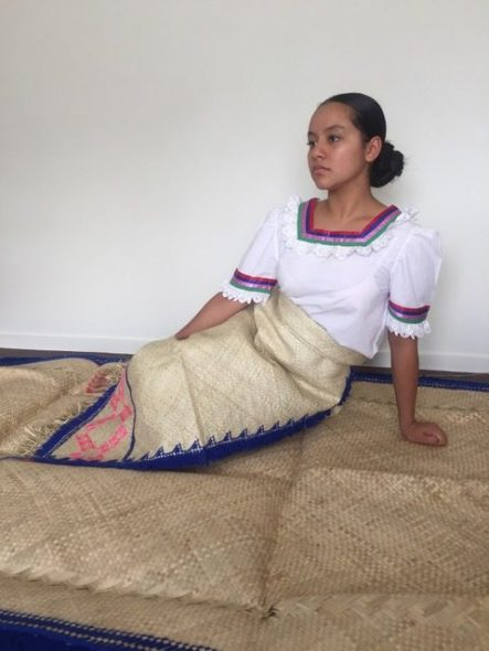 Woman with a white top and a woven flax skirt sitting on a flax mat, , with a cream wall behind her.