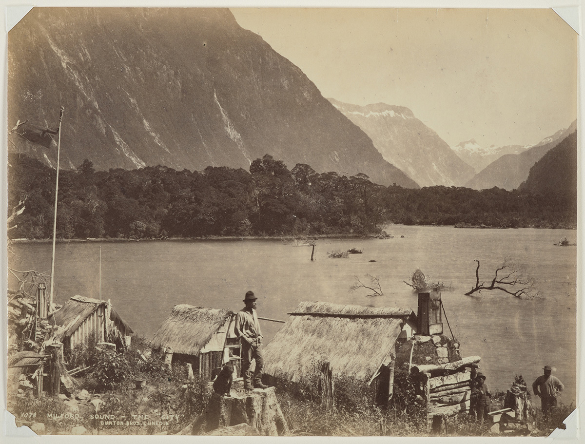 Sepia photo of lake with mountains in the background and some people in outside huts in the foreground