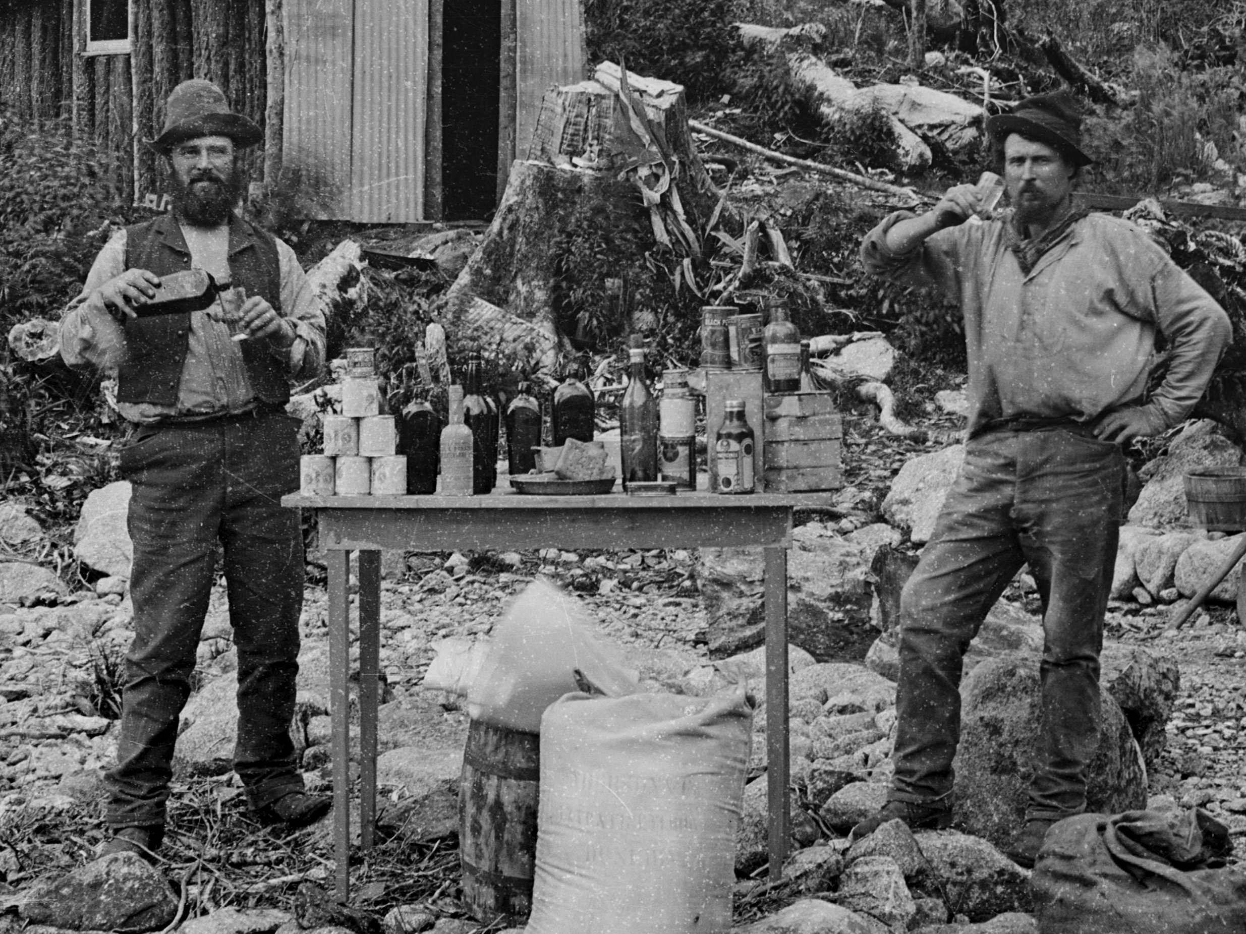 Black and white photo of two men at a campsite with tin huts and bush in the background. The men have full bottles in their hands and a table of bottles and food between them.