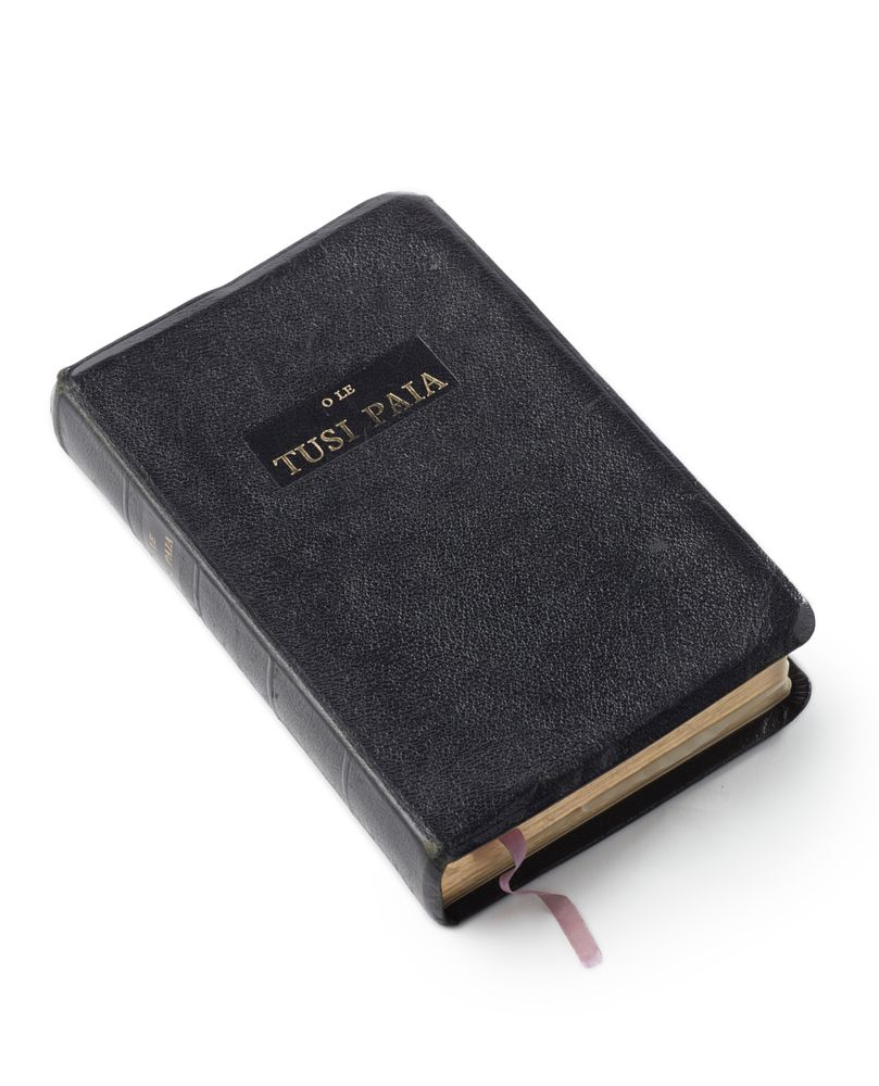 A black, leather-bound book on a white background. The gold writing on the front is in Sāmoan and says O le tusi paia. It has a pink ribbon at the base.
