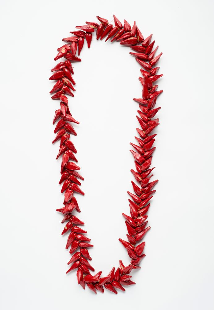 A red necklace made from closely strung pandanus pods. It is sitting on a white background.