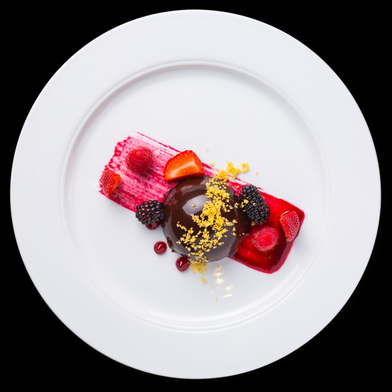 A white plate with a chocolate dessert with berries, berry juice and lemon zest sprinkled over it. The plate is on a black background