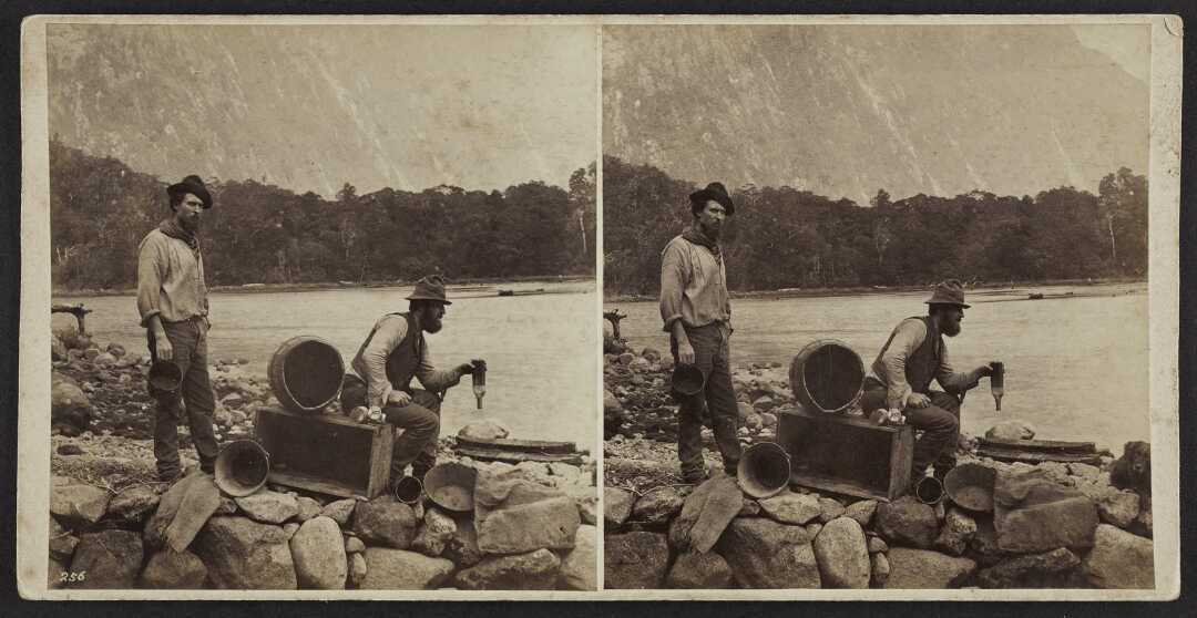 Twin sepia images of two men by the water with rocks in the foreground and dark hills in the background. The men have hats on and one is holding an empty bottle upside-down.