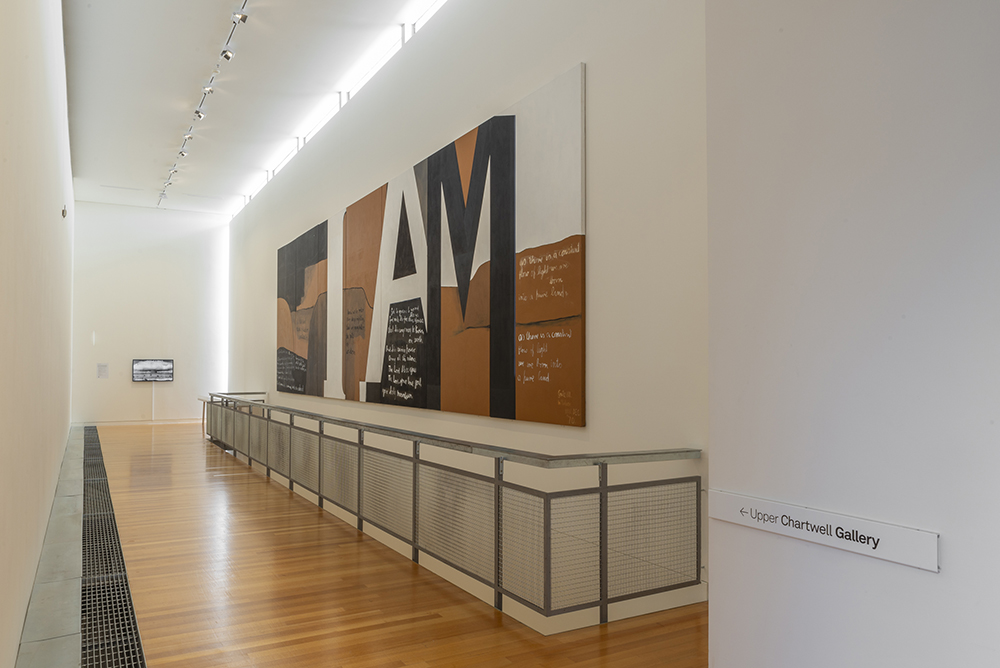 A long white room with a metal balcony and a brown, black and white painting on one wall.