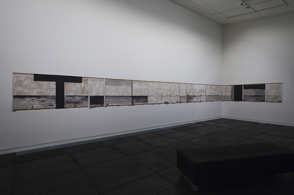A white corner wall with a long black, grey and brown painting stretched across it.