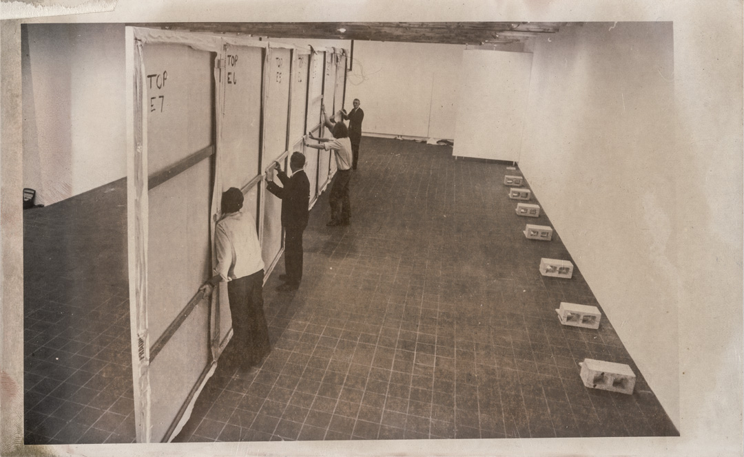 Black and white photo of four men installing a large painting.