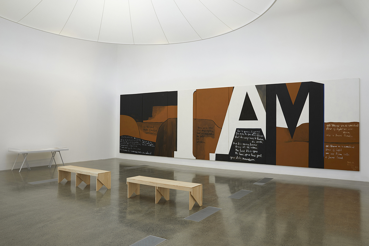 A white room with a large brown, black and white paiting in ti