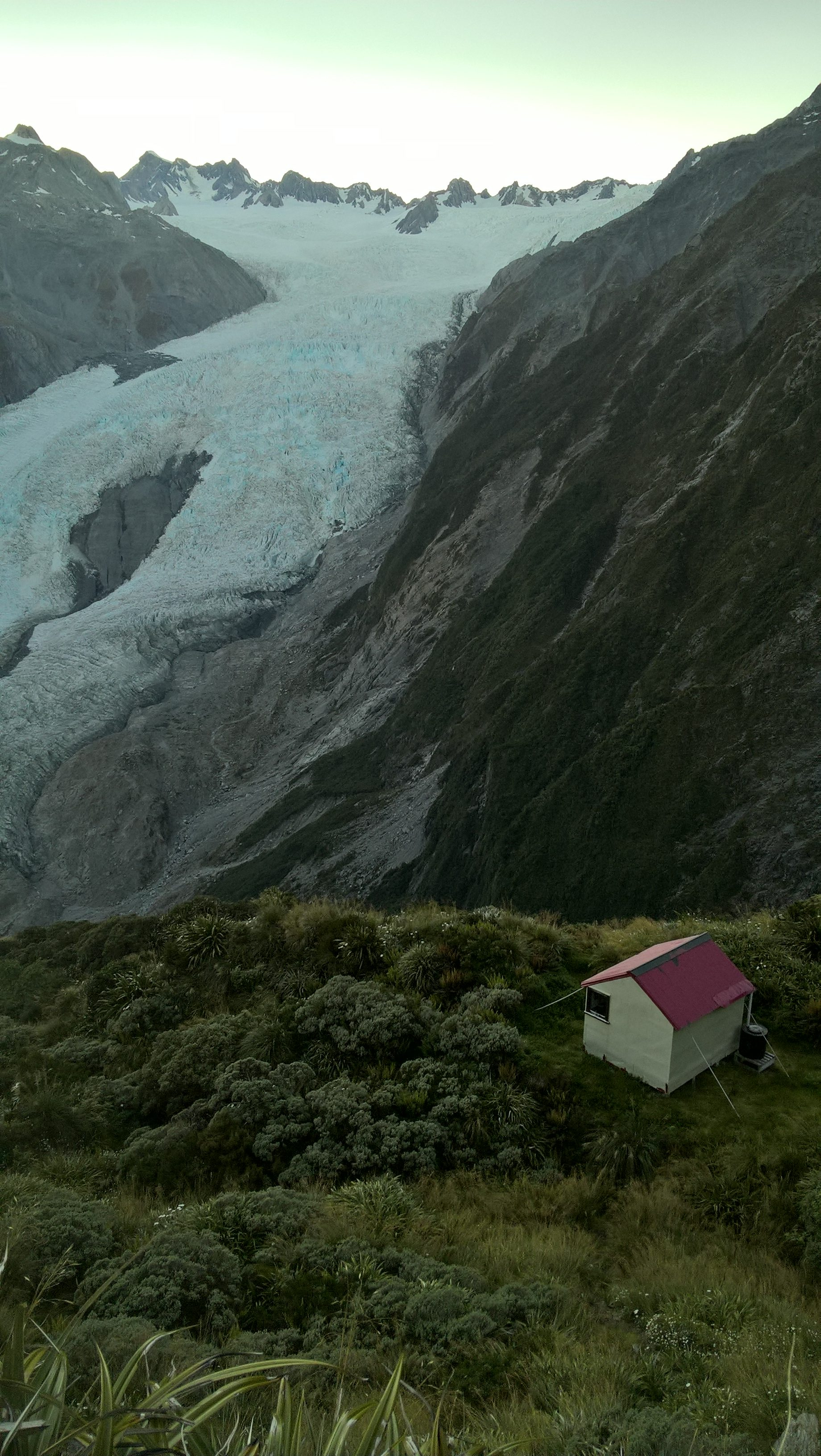 A glacier coming down the side of a mountain with a cream hut and a red roof in the foreground