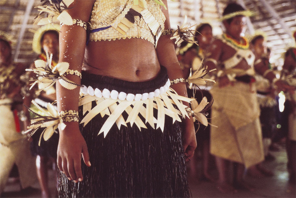 Close up of a woman, showing her dress and a belt made of coconut, shell, and palm frond