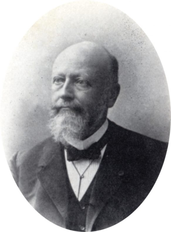 Black and white photo of a bald man in a bow tie with a beard and moustache