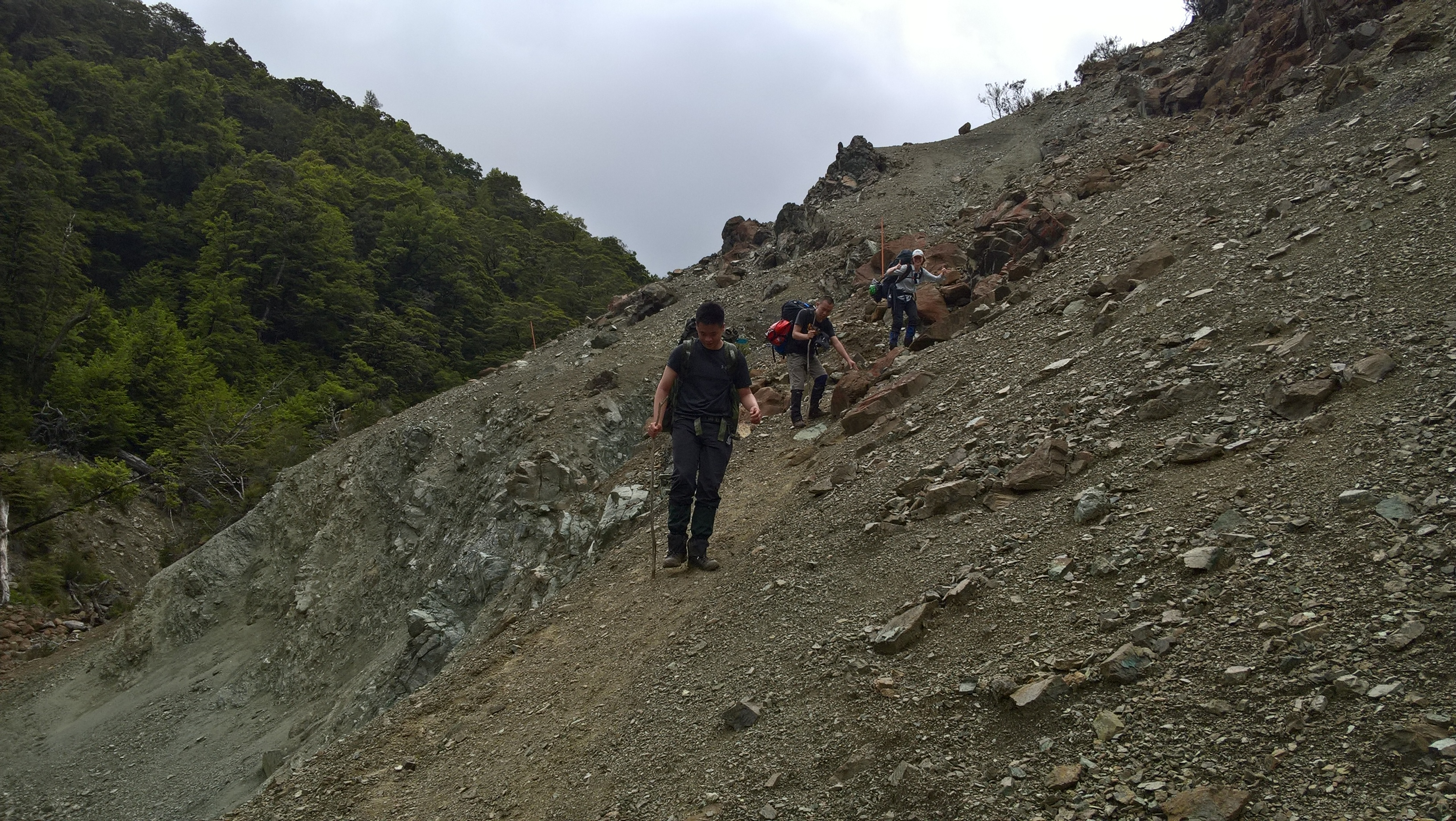 Three people descending a rocky path in the hills