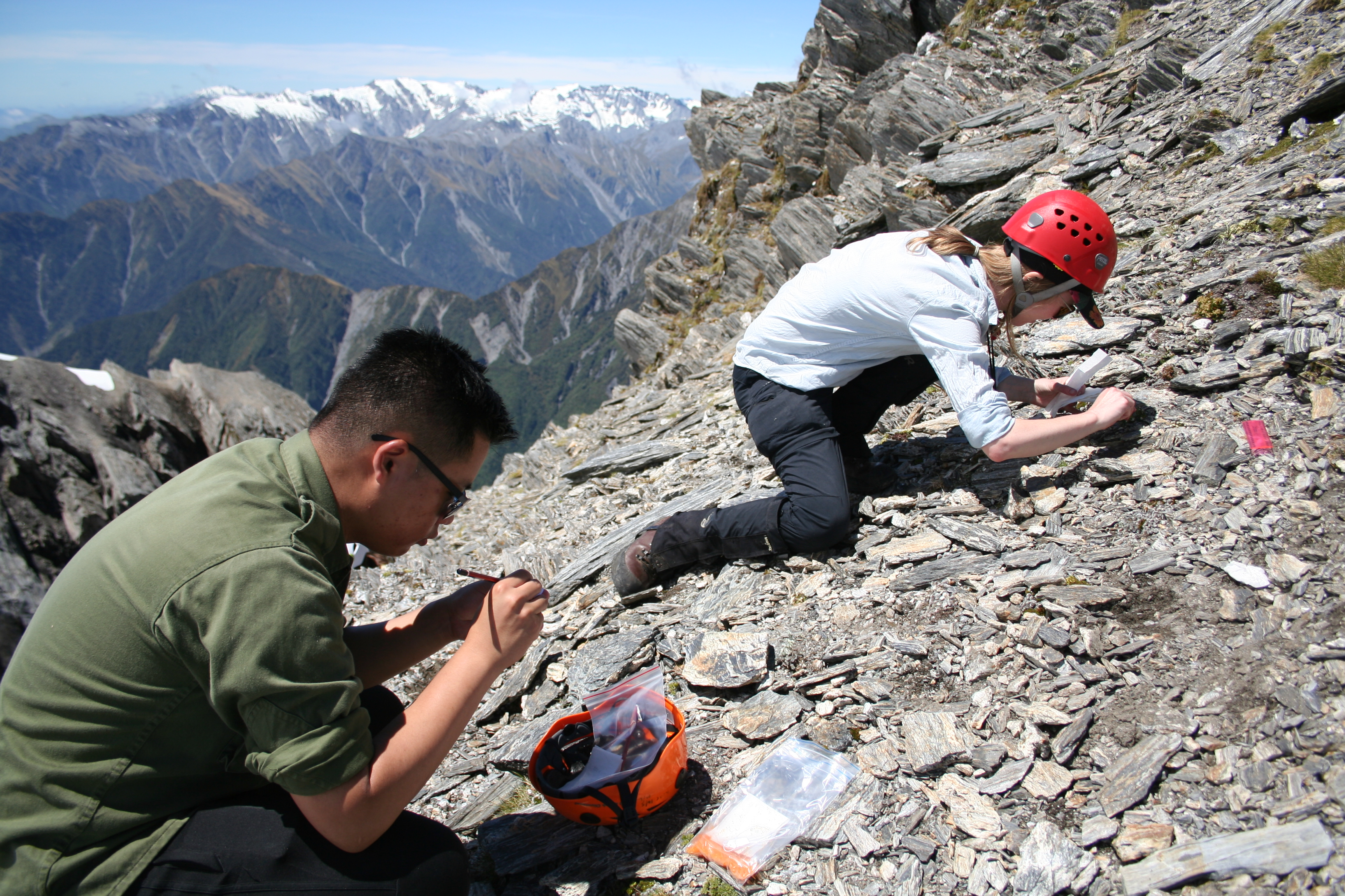 Two people crouched on the side of a mountain with pencils, bags and hard hats looking at the shale.