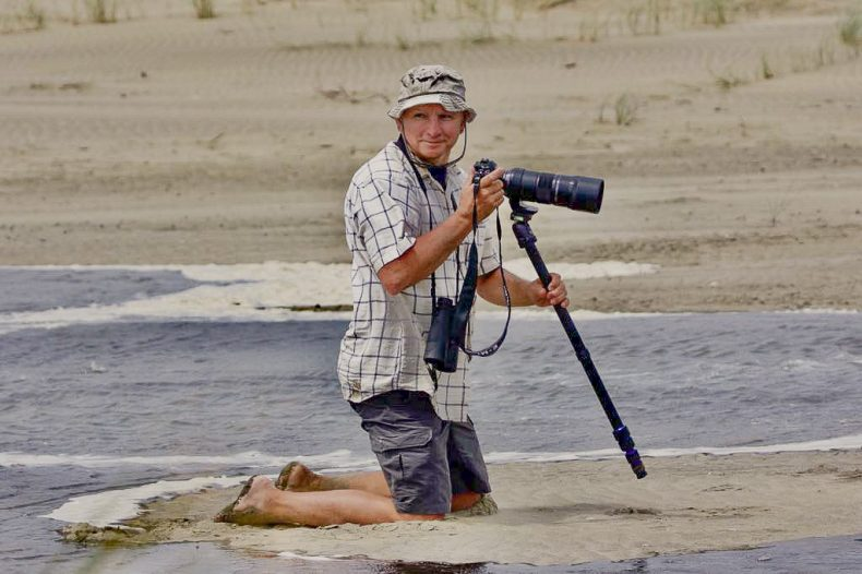 A man in a hat kneeling on the sand holding a camera and monopod