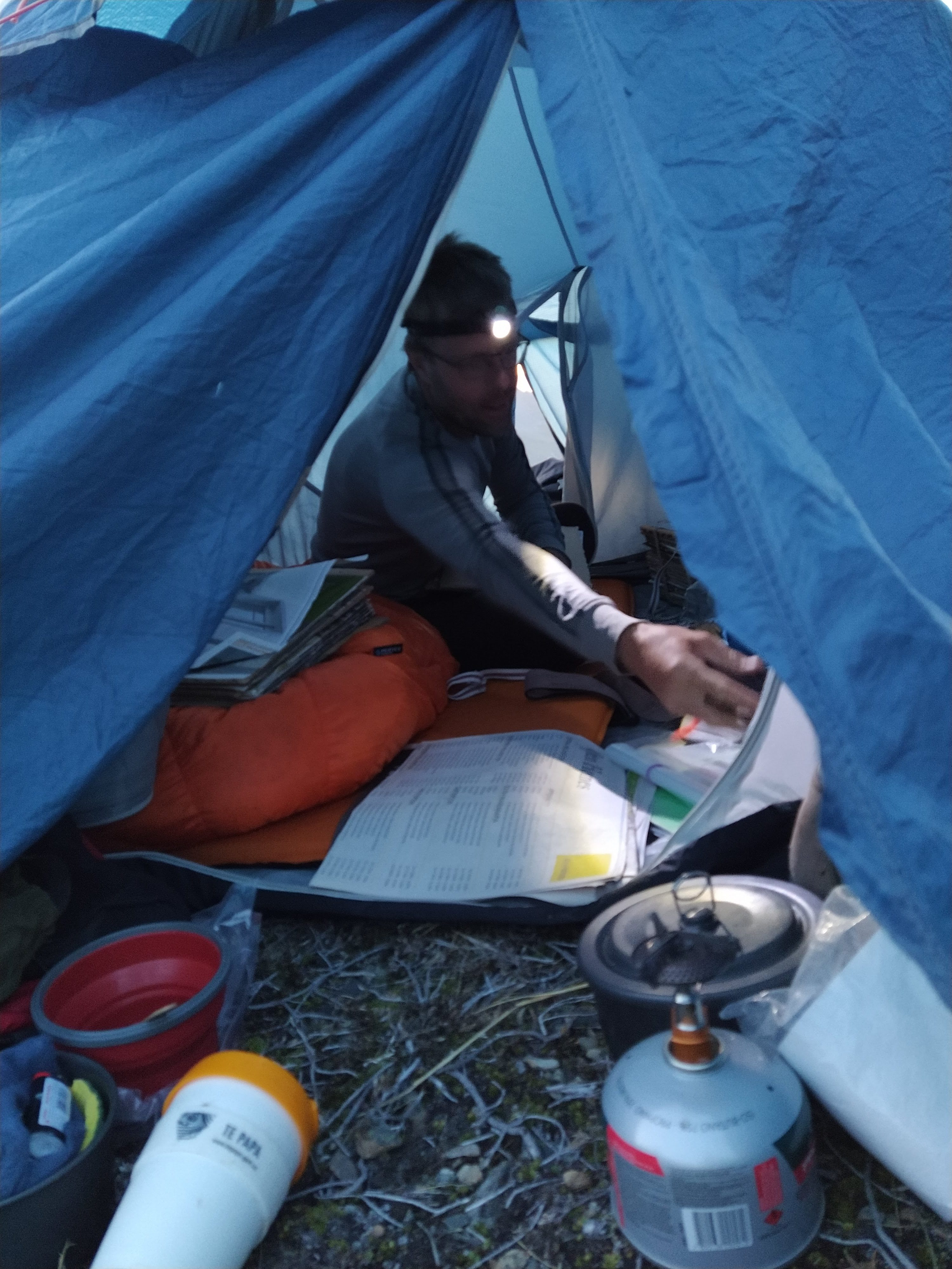 A man looking at maps and charts with a light on his head inside a tent with cooking gear in the foreground