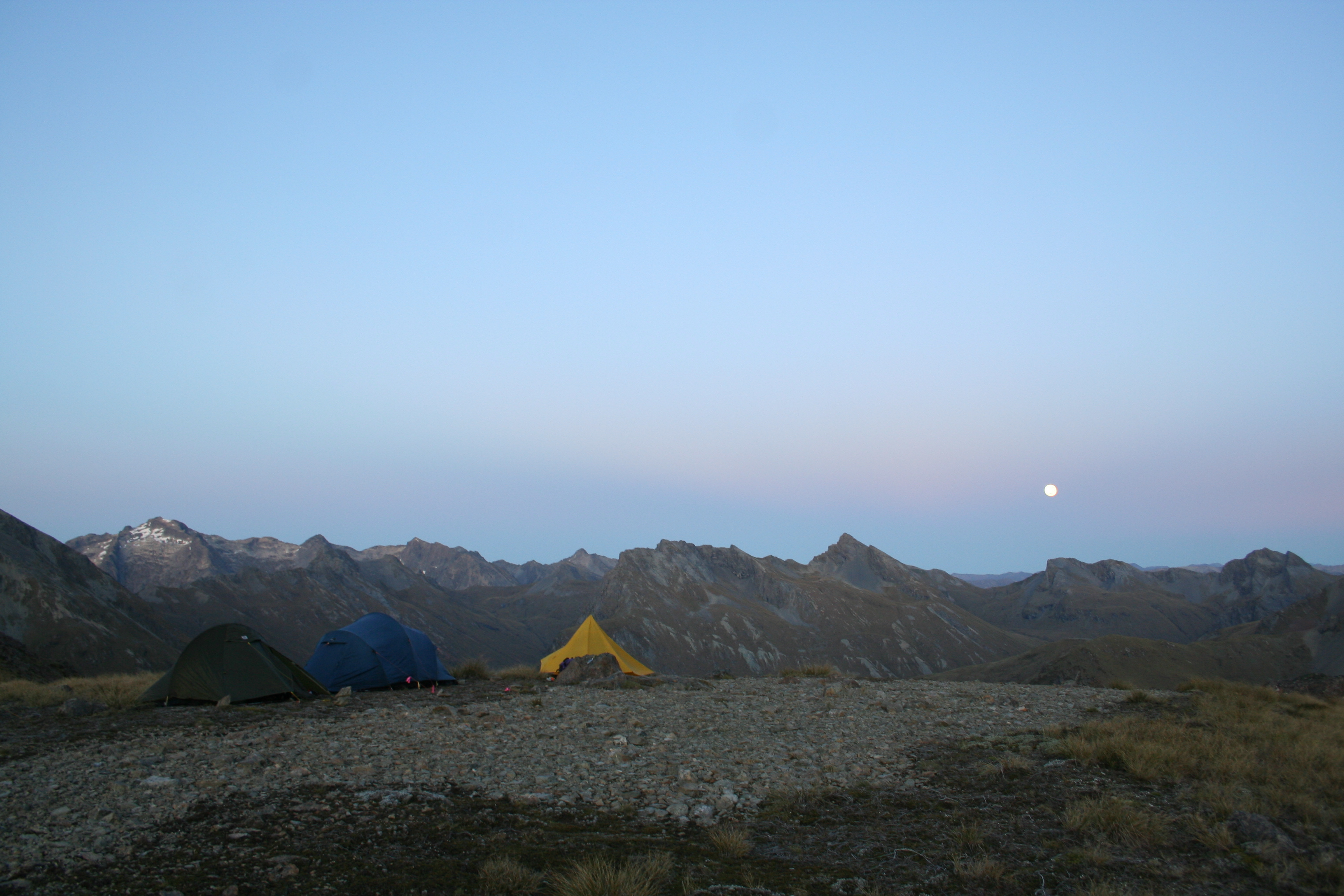 The moon rising over a mountain range with three tents in the foreground pitched on rocky ground
