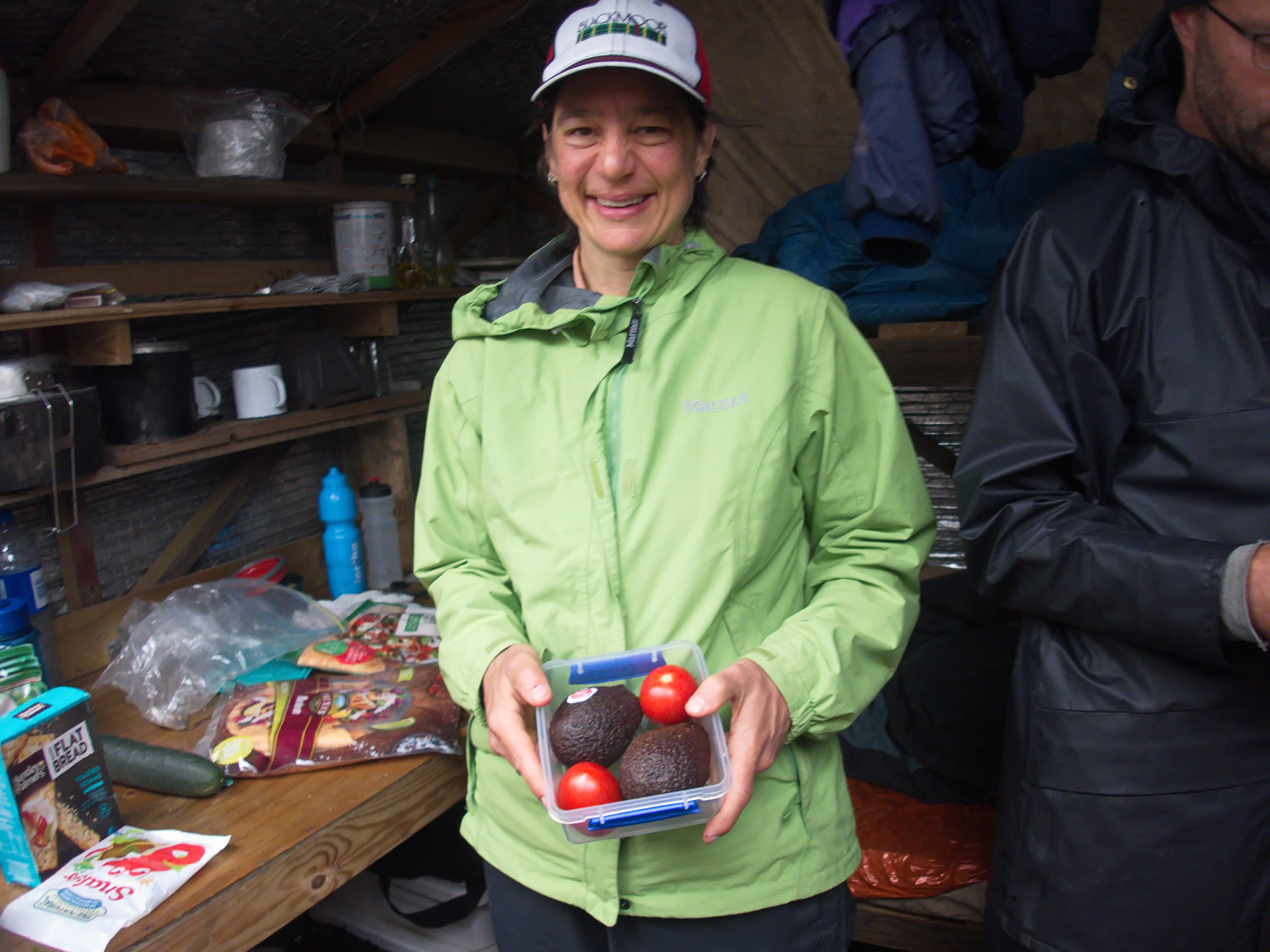 A woman wearing a cap and a green jacket inside a camping hut holding a container with two avocados and two tomatoes