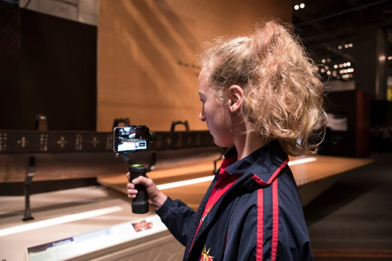 A young girl holding a camera in front of a screen.