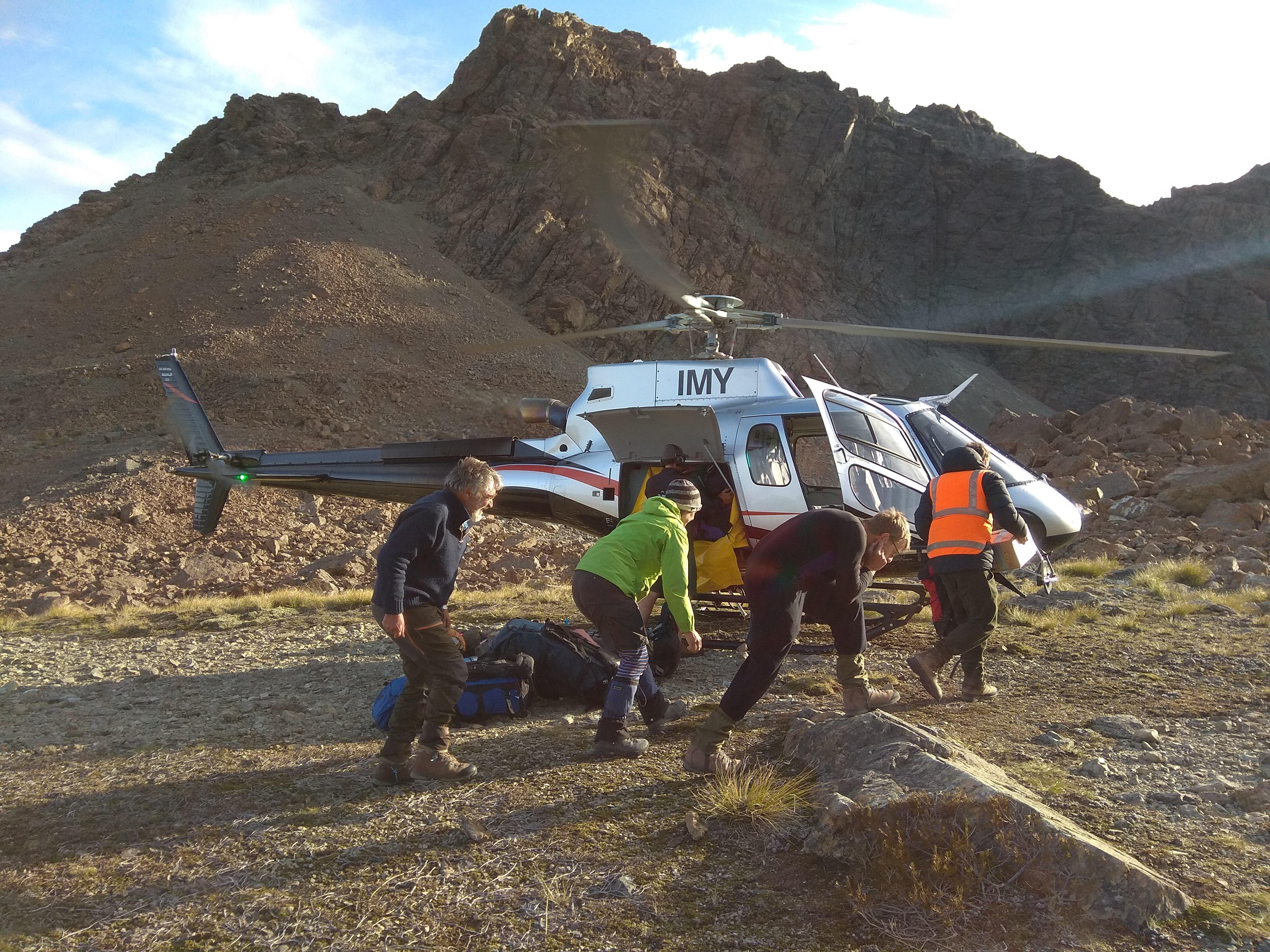 Four people crouched low in front of a helicopter in the mountains
