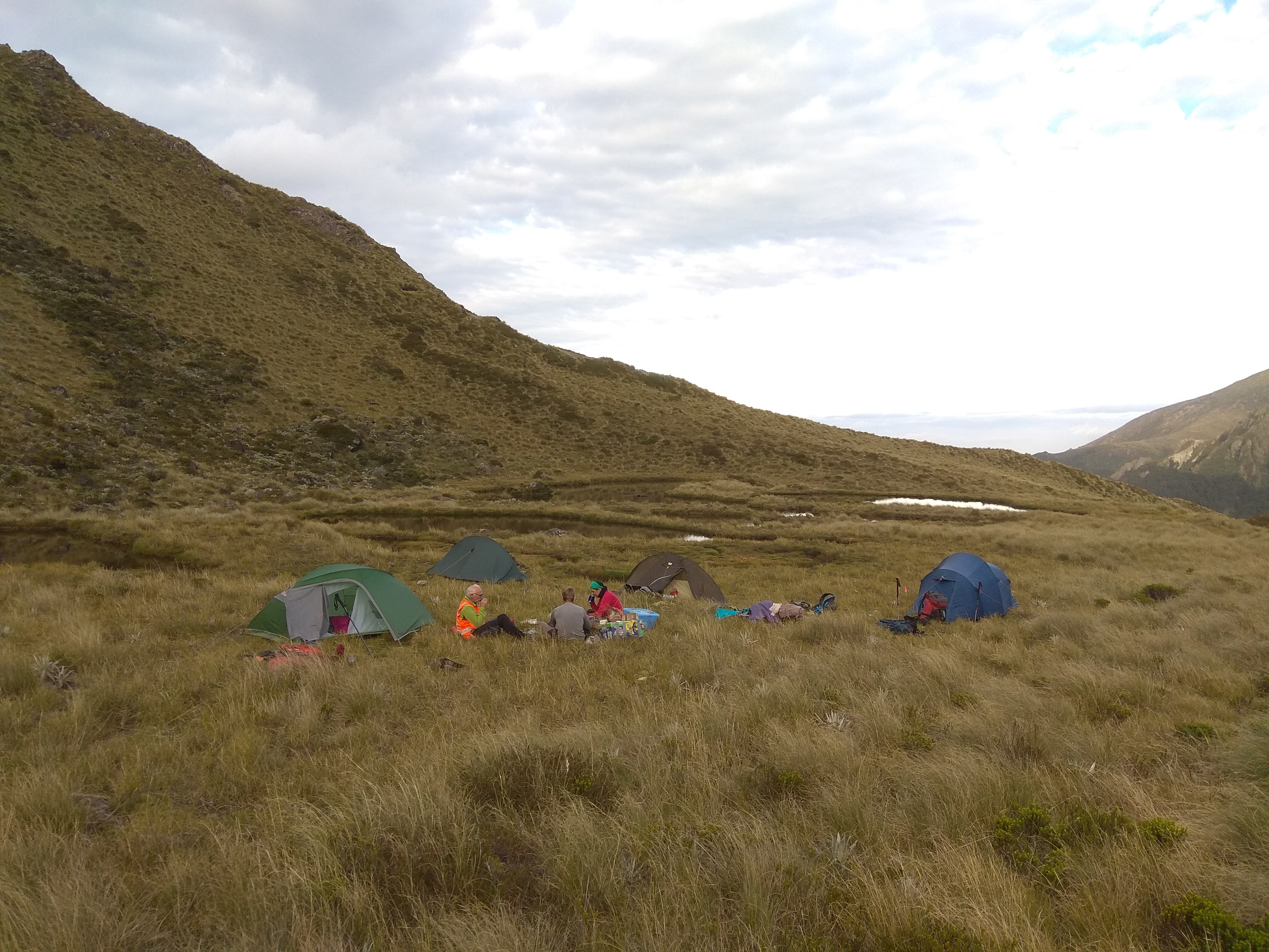 People sitting in the middle of a campsite surrounded by four tents on the side of a grassy mountain