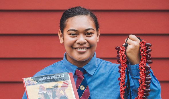 A teenage girl in a school uniform holding pandanus seed necklace and a booklet, standing in front of a dark red wooden wall
