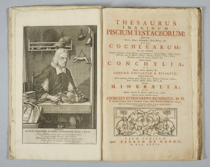 An open book with an engraving of a man in a science room on the left and text in red and black on the right-hand page