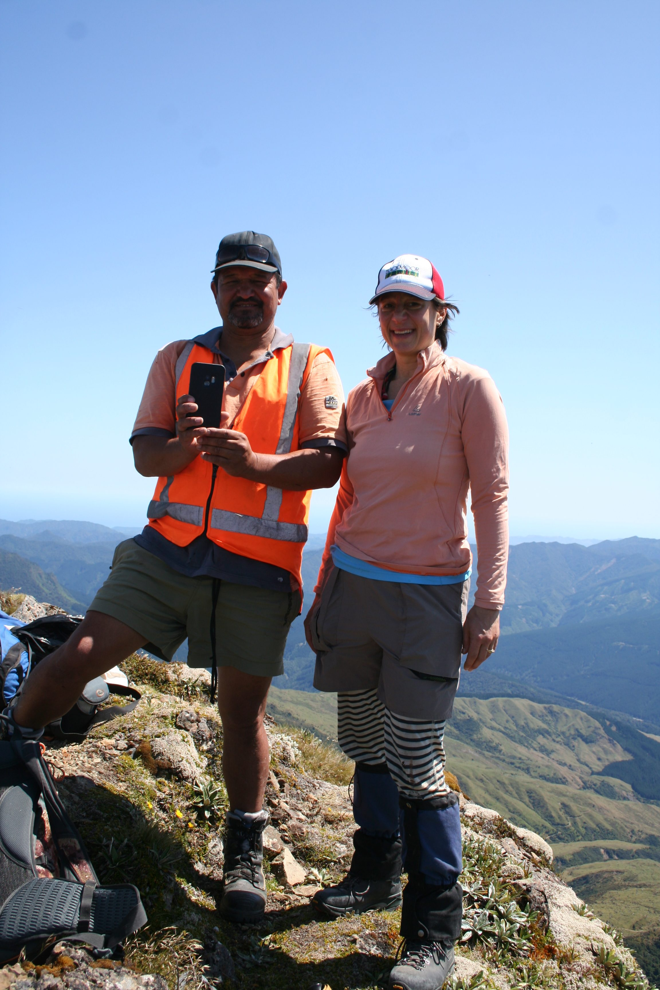 Two people in hiking gear and caps standing on the top of a mountain with blue sky and more mountains in the background. One person is holding a phone up and is wearing a high-vis vest