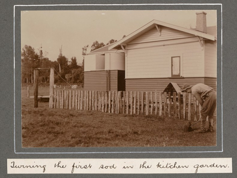 A sepia photo of a wooden house with a wooden fence in front of it and a man digging in the soil