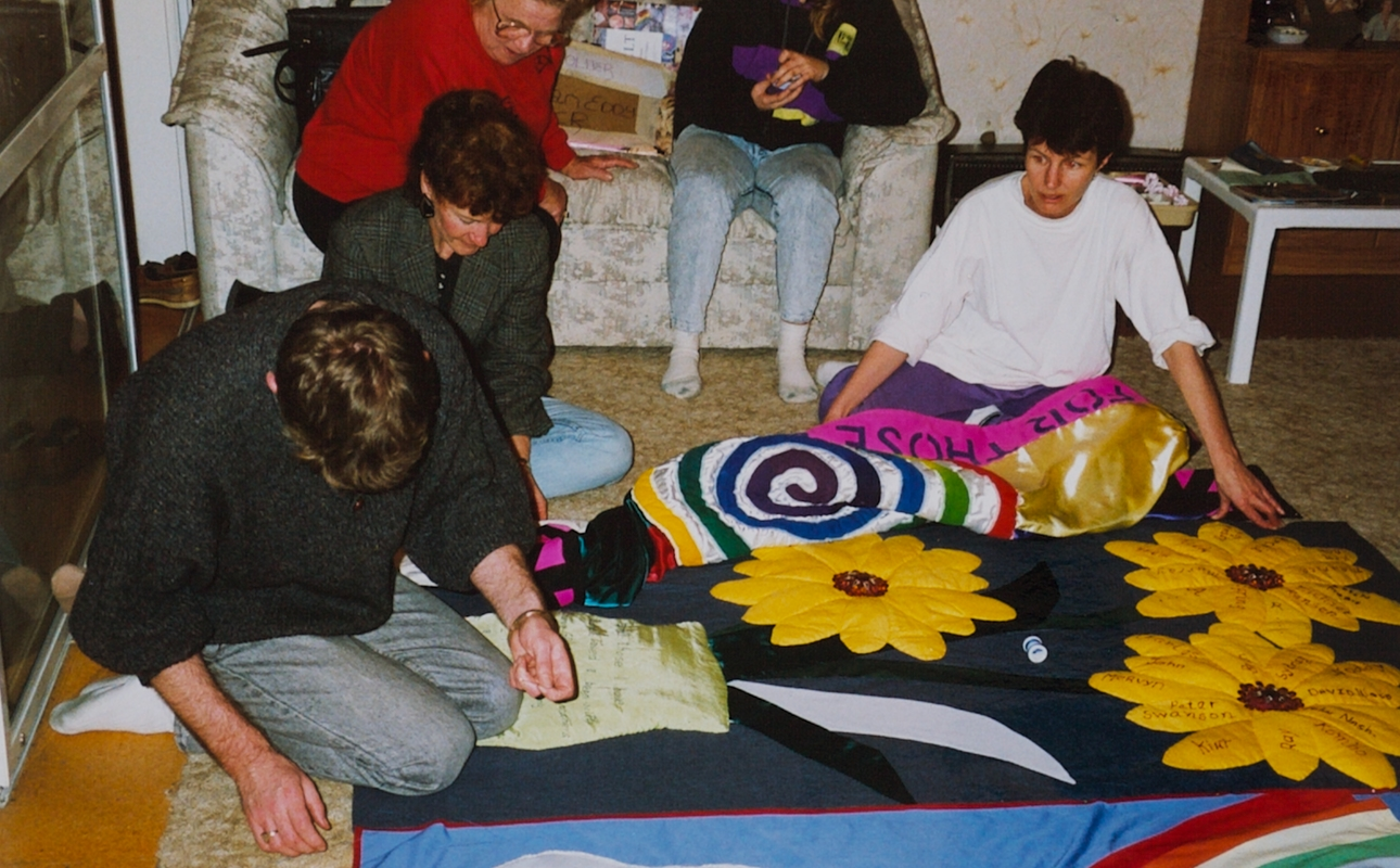 A group of people sitting on a floor working on a quilt